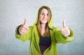 Pretty young girl with thumbs up over textured background  — ストック写真