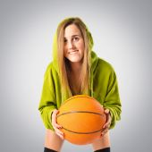 Blonde girl playing basketball over grey background — ストック写真