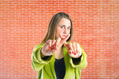 Girl doing NO gesture over bricks background  — Stock Photo