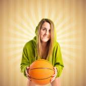 Blonde girl playing basketball over ocher background — Stock Photo