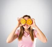 Girl with oranges in her eyes over grey background — Foto de Stock