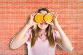 Girl with oranges in her eyes over bricks background — ストック写真