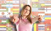 Young pretty woman pointing over flags background  — ストック写真