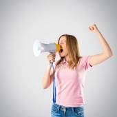 Blonde girl shouting with a megaphone over grey background  — ストック写真
