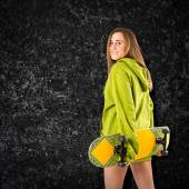 Skater with green sweatshirt over black background — Stock Photo