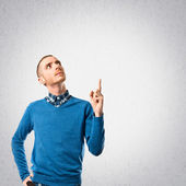Young man pointing up over grey background  — Stock fotografie