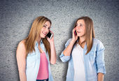 Young girls talking to mobile over textured background  — Stockfoto