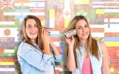 Friends talking through a tin phone over flags background — Stock Photo