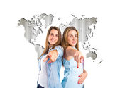 Girls pointing to the front over atlas background — Stock Photo