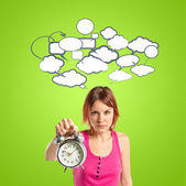 Serious redhead girl holding a clock over green background — Stock Photo