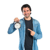 Man holding a clock over white background — Stock Photo