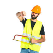 Workman with thumb down holding a hacksaw — Stock Photo