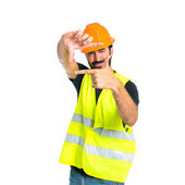 Workman focusing with his fingers on a white background — Stock Photo