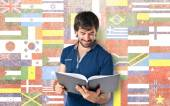 Man reading a book over flags background — Stock Photo
