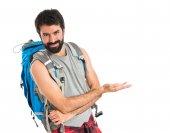 Backpacker presenting something over isolated white background — Stockfoto
