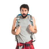 Backpacker doing surprise gesture over white background — Stockfoto