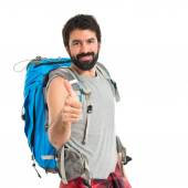 Backpacker with thumb up over white background — Stok fotoğraf