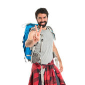 Backpacker doing victory gesture over white background — Stockfoto