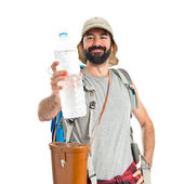 Backpacker drinking water over white background — Stock Photo
