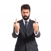 Businessman making horn gesture over white background — Stock Photo