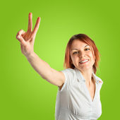 Young woman doing victory gesture over green background  — Stockfoto