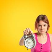 Serious redhead girl holding a clock over yellow background — Stock Photo