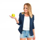 Blonde girl showing an apple over white background — Стоковое фото