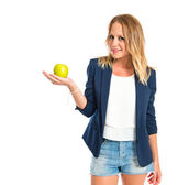 Blonde girl showing an apple over white background — Stockfoto