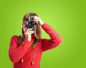 Woman photographing over green background — Stock Photo
