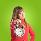 Woman holding a clock over green background — Stock Photo