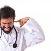 Doctor covering his ears over white background — Stock Photo