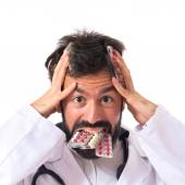 Frustrated doctor with pills over white background — Stock Photo