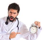 Surpreso médico segurando um relógio sobre fundo branco — Fotografia Stock