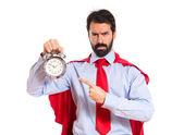 Businessman dressed like superhero holding a clock — Stock Photo