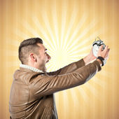 Young businessman holding an antique clock over ocher background  — Stock Photo