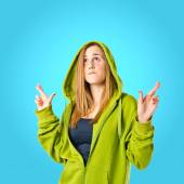 Pretty girl with her fingers crossing over blue background  — Foto de Stock