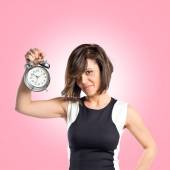 Pretty woman holding an antique clock over pink background — Stock Photo