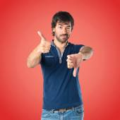 Man doing a bad signal over red background — Stock Photo