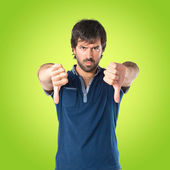 Man doing a bad signal over green background — Stock Photo