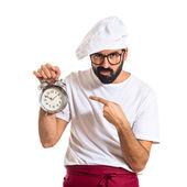 Chef holding a clock over white background — Stock Photo