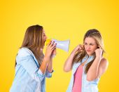 Girl shoutimg with a megaphone at her friend — Stock Photo