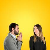 Men pleading at his girlfriend over yellow background  — Stock Photo