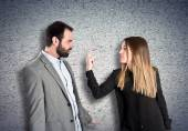 Girl doing the horn sign at her boyfriend over textured background  — Stockfoto