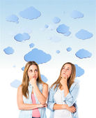 Girls thinking over clouds background — Stock Photo