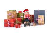 Blonde christmas kid around several presents — ストック写真