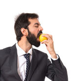 Businessman eating an apple over white — Stock Photo
