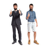 Twin brothers doing victory gesture over white background — Stockfoto