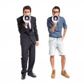 Brothers shouting by megaphone over white background — Stockfoto