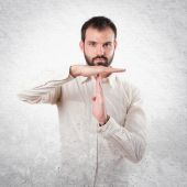 Young man doing the timeout sign over white background — Stockfoto
