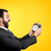 Young businessman holding an antique clock over yellow background — Stock Photo
